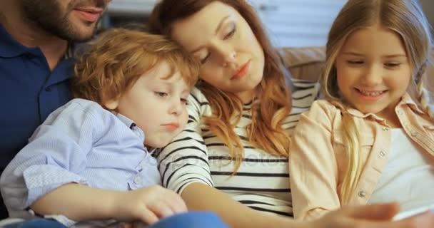 Madre, padre, figlio e figlia facendo uso della compressa, giocare e divertirsi. Famiglia di trascorrere del tempo insieme a casa. Famiglia felice