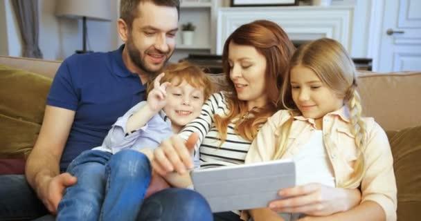 Madre, padre, figlio e figlia utilizza tablet, guardare film. Famiglia di trascorrere del tempo insieme a casa. Famiglia felice. Facce buffe