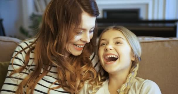 Happy attractive woman with her daughter spending time together at home on the couch. Mother and daughter smiling, hugging and laughing.