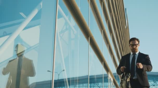 Attractive caucasian businessman looking at the watch and running to the meeting near office building center. Man late for work, meeting. Slow motion. Close up