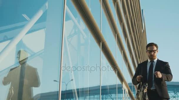 Atractivo empresario caucásico mirando el reloj y que la reunión cerca de edificio centro de oficinas. Hombre tarde para trabajo, reunión. Cámara lenta. Cierre para arriba