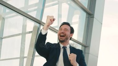 Happy attractive businessman raising hands. Happy emotions. Good news. Outdoors near office windows. close up