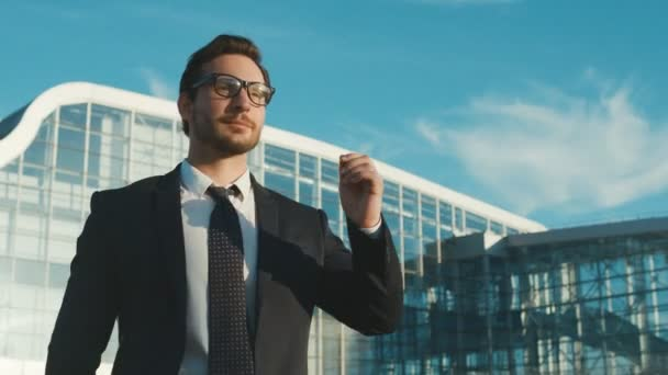 Confident attractive caucasian businessman walking outside near big office center building, taking off glasses, smiling and raising hands. Close up. portrait shot