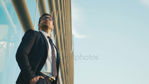 Portrait of worried businessman standing outside the office building, waiting car, looking at the watch. Close up