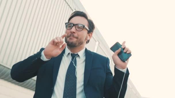 Happy pohledný podnikatel poslechu hudby ve sluchátkách na smartphone, chodit mimo kancelář a legrační tanec v rytmu. Zábavné taneční pohyby. Detailní záběr