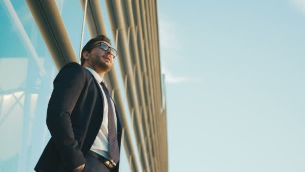 Portrait of worried businessman standing outside the office building, using smartphone, waiting car, looking at the watch. Close up