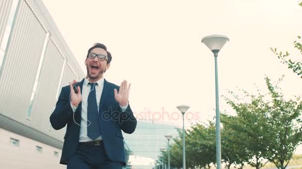 Happy pohledný podnikatel poslechu hudby ve sluchátkách na smartphone, chodit mimo kancelář a zábavné tance