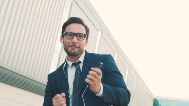 Happy atraktivní podnikatel poslechu hudby v sluchátka na smartphone, pěší poblíž kancelářská budova a legrační tanec v rytmu. Zábavné taneční pohyby, hraje na kytaru. Detailní záběr