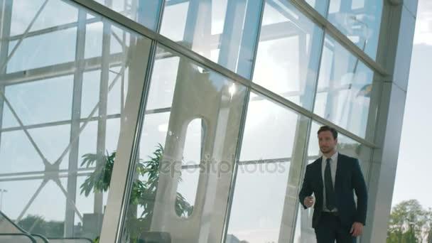 Confident stylish businessman walking near big office windows outdoors. portrait shot. Slow motion