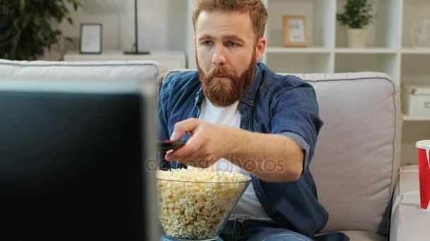 Portré, fiatal ember ül a kanapén, a pattogatott kukorica, kapcsolja be a tv, és elkezd néz film otthon.