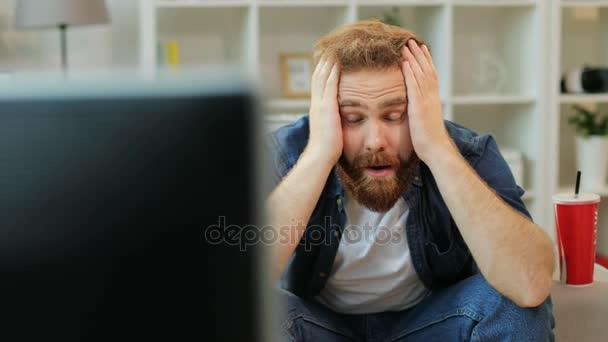 Érzelmi ember nézi labdarúgó mérkőzés a pattogatott kukorica és kóla coca közben ül a kanapén, otthon a nappaliban.