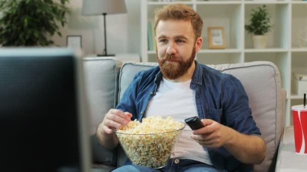 Fiatalember kapcsolási csatornákat és talál érdekes filmek a tévében, sit kényelmes és kezdő enni popcorn a living Room.