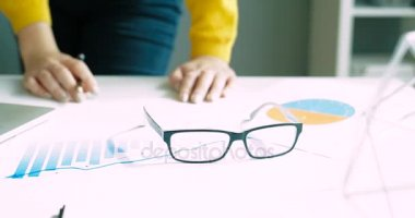 Beautiful woman putting on a pair of glasses and working with financial charts at the office. Close up woman putting on glasses. Close up. Business project