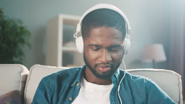 Attractive black african man listening to music in big white headphones while sitting on the couch at home. Slow motion. Close up