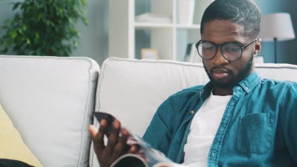 Mladí africké muž v brýlích, modré košili na bílé pohovce prohlížení časopisu pro nakupování. Vnitřní