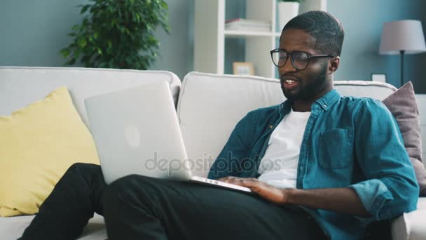 Young african-american man in glasses sitting on the sofa using laptop at home on the floor for chatting with friends. Indoor.