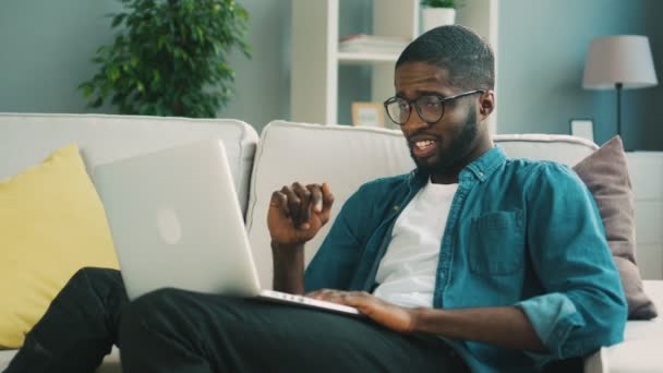 Young beautiful african man sitting on sofa using laptop for video chatting with friend on living background. Indoor.