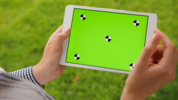 Tartó női fehér táblaszámítógép berendezés-val zöld képernyő háttér zöld fű. Kint a parkban. Nő, görgetés, nagyítás, érintőképernyő megérintésével. Chroma-kulcs. Közelről. Mozgás követése