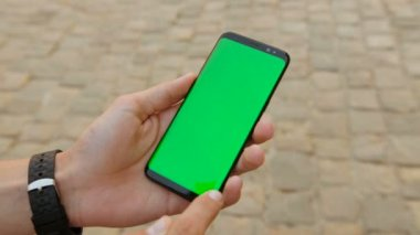 Man holding black smart phone with green screen on city street background on sunny day. & Man touch smart phone in the tent. First open the tent touch ...