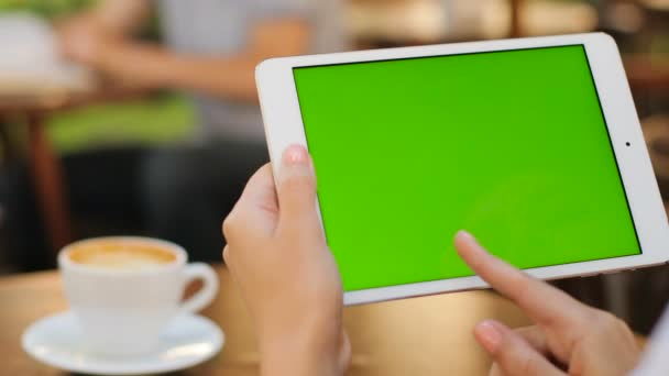 Female hands holding white tablet computer device with green screen while sitting outdoors in the cafe. Woman scrolling. zooming on touchscreen. Horizontal. Woman drinking coffee. Close up. Chroma key