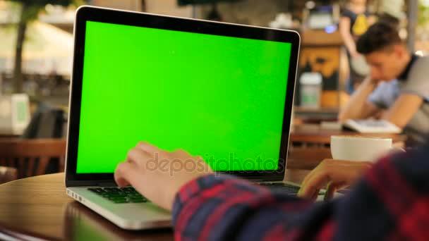 Nő laptop számítógép használata a zöld képernyő ülve kívül a kávézóban. Női kéz a laptop billentyűzet gépelés. Közelről. Chroma-kulcs
