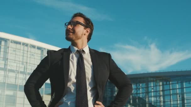 Portrait of attractive young businessman standing outdoors near office center building, looking around and at the camera, doing thumbs up and smiling. Close up