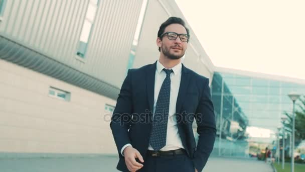 Attractive stylish businessman walking near office center building and taking off glasses and looking straight at the camera. close up. Portrait