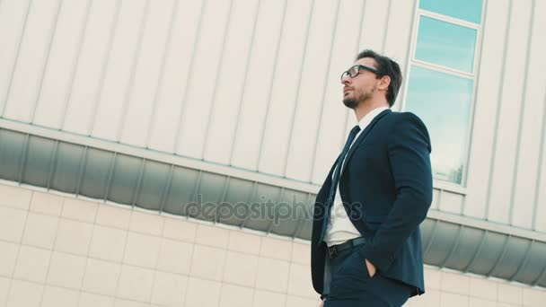 Attractive stylish businessman walking near office center building and taking off glasses. close up. side view