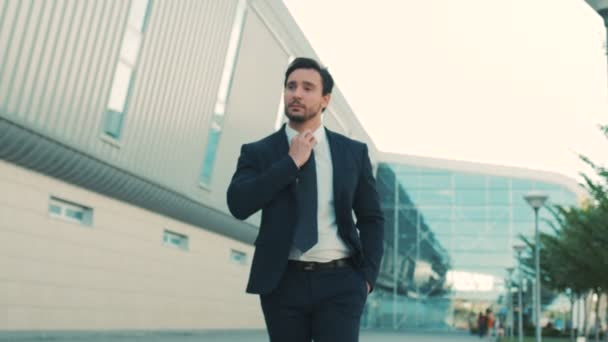 Young attractive stylish businessman walking near office center building and looking straight at the camera. close up. portrait shot