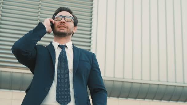 Moda Uomo Ufficio : Giovane alla moda uomo di affari comunica sul telefono mobile