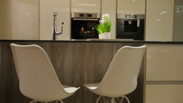 View of light stylish kitchen in the modern style with white wooden table with white chairs. Close up.