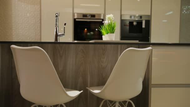 Pohled na lehké stylové kuchyně v moderním stylu s bílými dřevěný stůl s bílými židlemi. Detailní záběr