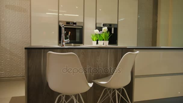 View of light stylish kitchen in the modern style with white wooden table with white chairs.