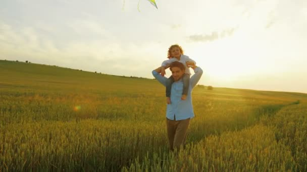 Happy father with son running in green wheat field on sunset. Young father holding his son on the shoulders. Boy playing with flying kite. Close up