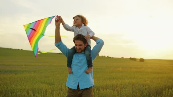 Happy family of young father walking in green wheat field with his son on the shoulders. Kid playing with flying kite. Sunset