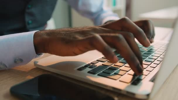 Black african american typing on the laptop keyboard in the office. Close up male hands typing on keyboard.