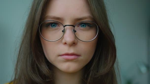 Portrét dospívající dívky v brýlích při pohledu na fotoaparát a usmívá se cheerfuly. Detailní záběr