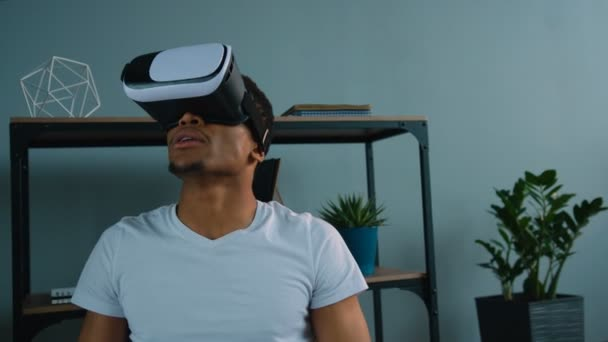 Black african american man using vr headset at the office. Exited man looking aroung and touching virtual objects
