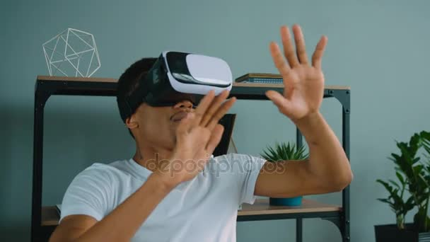 Black african american man using vr glasses at the office. Exited man looking aroung and touching virtual objects
