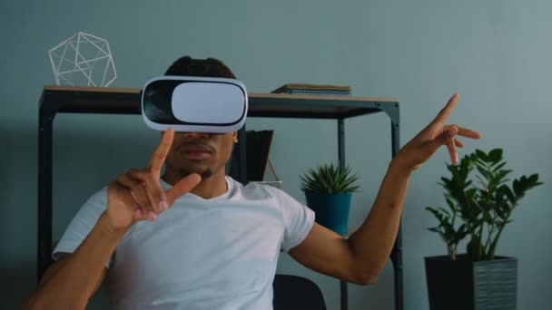 African american man using vr glasses at the office. Exited man looking aroung and touching virtual objects