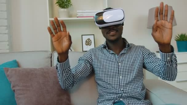 Black african american man using vr headset at the couch in the living room. Exited man looking aroung and touching virtual objects