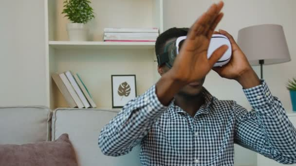 Black african american man using vr headset at home on the couch. Exited man looking aroung and touching virtual objects