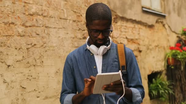 Stylish young african american man in glasses with earphones using tablet for chatting with friend standing near wall in city.