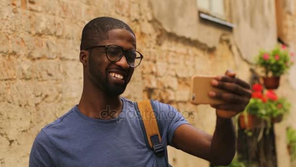 Pohledný mladý Američan Afričana muž v brýle video chatování s přáteli pomocí mobilního telefonu na pozadí města