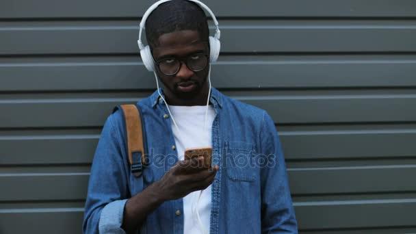 Stylový mladý africký americký turista poslechu hudby pomocí sluchátek a chytrý telefon. Venkovní.