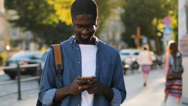Young african tourist in blue shirt using smart phone, looking to the camera and smiling with teeth standing city center. Outdoor.