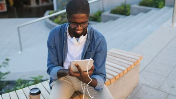 Attractive african man with glasses and headphones using tablet and drinking coffee while sitting on the bench on background with stairs.