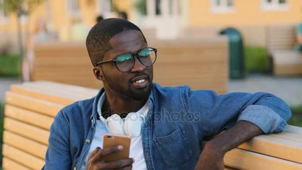 Portrét mladé africké člověka v brýlích s sluchátka pomocí chytrého telefonu pro chatování s přítelem sedící na lavičce v městě.