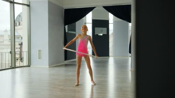 Mladí attcactive sportovní dívka v růžové těle dělat cvičení gymnastiky přepážku v ateliéru