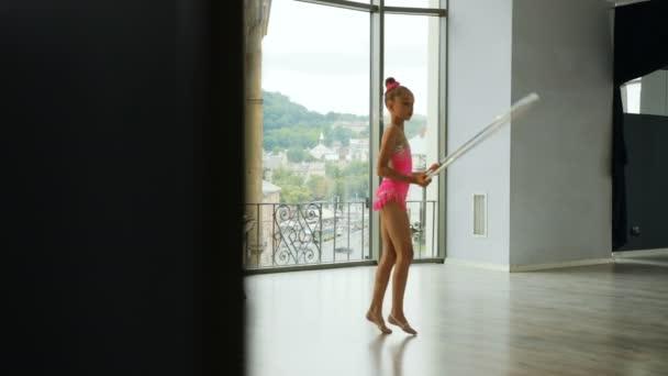 Mladí attcactive dívka v růžové těle školení cvičení gymnastiky přepážku v ateliéru na nadmořské výšce město